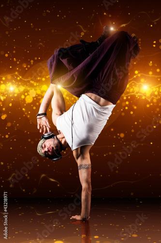 männlicher Tänzer vor Lichterhintergrund beim Handstand