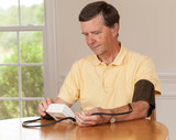 Senior man taking blood pressure at home