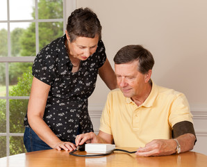 Senior man taking blood pressure with wife