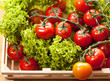 Tomatoes and salad in  wooden basket on the table