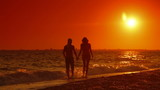 Couple Walking Along Summer Beach at Sunset