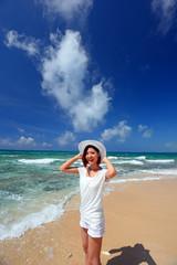 沖縄の海辺で寛ぐ笑顔の女性