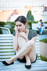 Depressed young woman sitting in a park full of happy couples