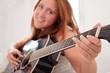Junge Frau spielt Gitarre im Bett