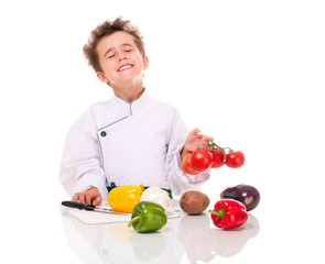 Little boy chef in uniform with knife cooking vegatables holding
