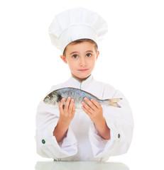 Little boy chef in uniform presenting dorado fish