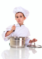 Little boy chef in uniform with ladle stiring in the pot