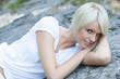 Hübhsche Frau liegt auf Felsen