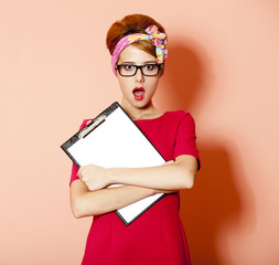 Style redhead girl in glasses and board at pink background.