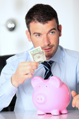 man with pink piggy bank and one dollar bill