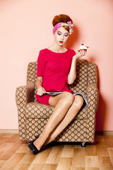 Style girl in red dress sitting in armchair with cake and magazi