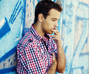 Young teen boy smoking near graffiti wall.