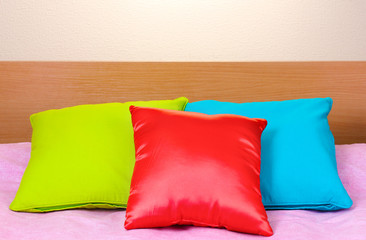 bright pillows on bed on beige background