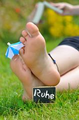 Füße mit Sonnenschirm im Urlaub