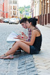 Girl and guy sitting on the road with a map.