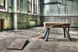 Dilapidated pommel horse in an abandoned school gymnasium poster