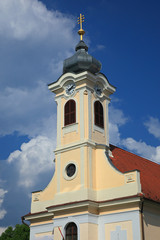 Church tower with clock against cloudy blue sky