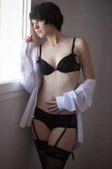 Pretty brunnete looking throught the window in lingerie