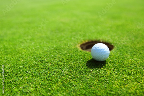 golf ball on lip of cup - 43247561