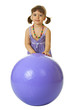 Little girl with a large rubber ball on white