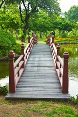 Nice old wooden bridge in park at summertime.