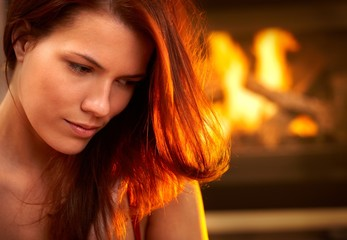 Portrait of attractive woman in front of fire
