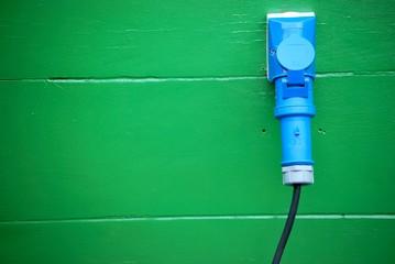 Blaue Steckdose an einer Holzwand