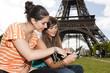 2 jeunes filles regardant un portefeuille devant la Tour Eiffel