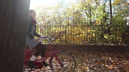 Gorgeous girl riding red bike on autumn leafs