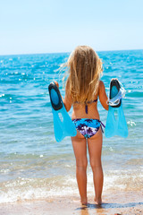 Cute girl facing the sea with goggles and flippers.
