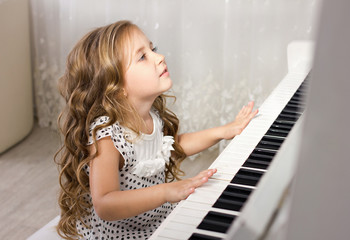 beautiful blond little girl  learn from playing near a piano