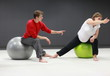 Detaily fotografie pregnant woman with  personal trainer on large  stability balls