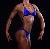 Muscular female torso on black background