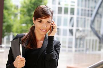 Femme d'affaire arrivant au bureau en étant au téléphone
