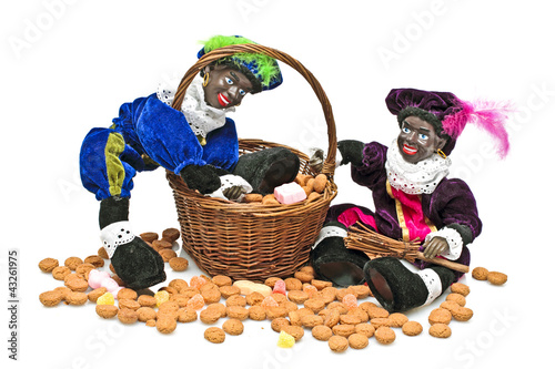 Two black piet with a basket full of gingernuts and sweets