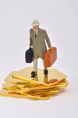 Geschäftsmann mit Koffern auf Goldbarren