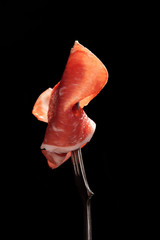 Parma ham on fork isolated.