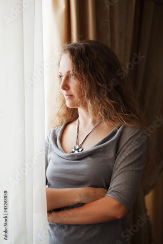 Sad beautiful woman looking through the window