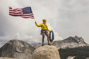 Climber raising the flag on the summit.