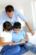 Father controlling children while playing on tablet