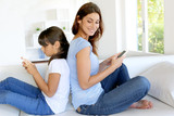 Mother and daughter using mobile phone at home