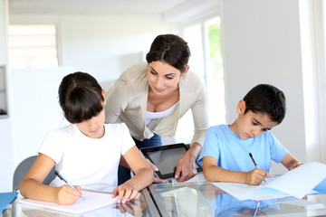 Teacher and kids in classroom writing on notebook