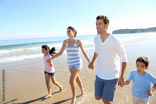 Family having fun running on the beach