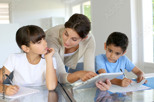 Woman teaching class to school children with digital tablet