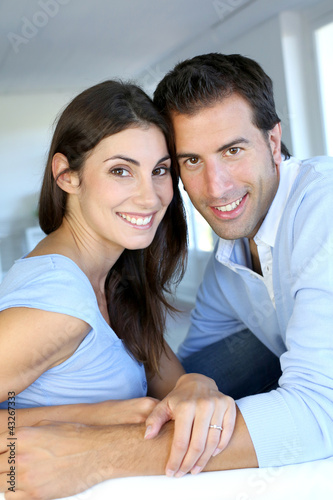 Closeup of cheerful couple sitting in sofa