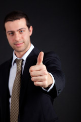 Businessman making ok sign on black background