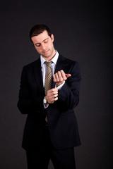 Businessman adjusting his look isolated on black