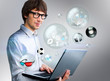 Handsome man holding laptop. Different objects are flying from t