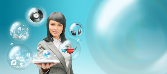 Pretty business woman holding tablet computer and different obje