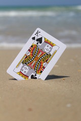 The king card in the sand, beach background